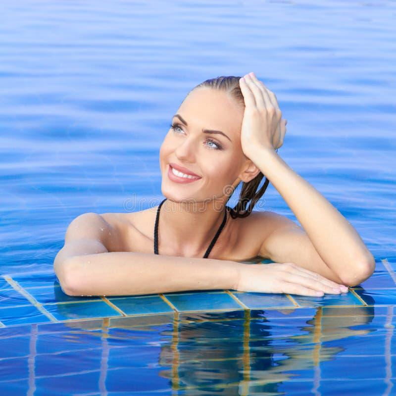 Mujer sonriente reflejada en piscina fotografía de archivo