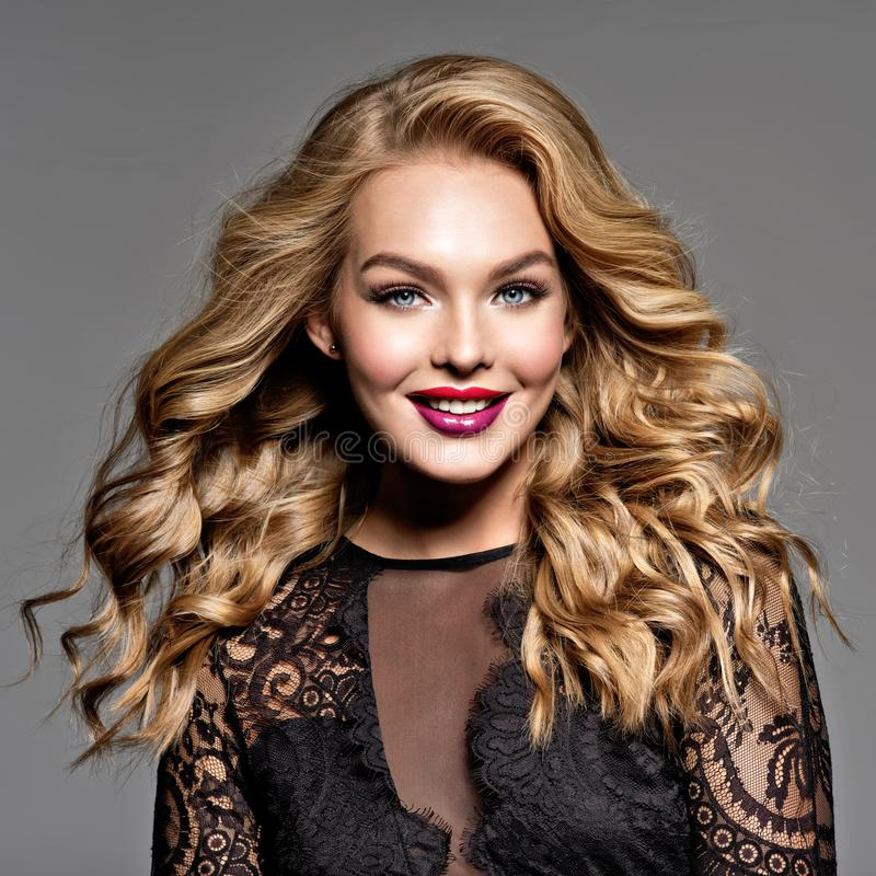 Mujer sonriente rubia con el pelo hermoso rizado largo imagenes de archivo
