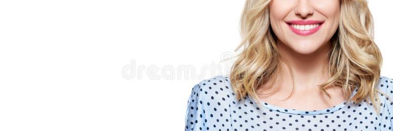 Mujer sonriente rubia joven hermosa con la piel limpia, el maquillaje natural y los dientes blancos perfectos aislados sobre el f foto de archivo libre de regalías
