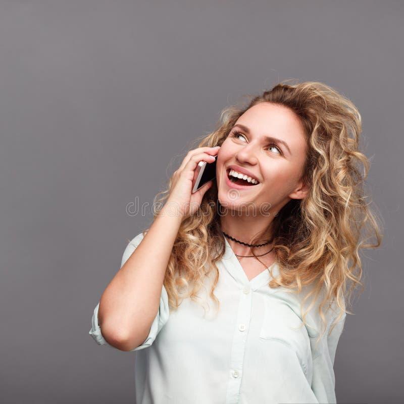 Mujer sonriente taling en el teléfono imágenes de archivo libres de regalías