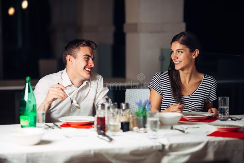 Mujer sonriente una fecha en un restaurante, teniendo una conversación sobre una comida en hotel foto de archivo