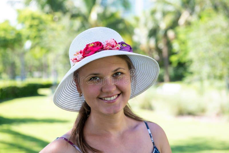 Mujer sonriente usando sombrero frente a las palmas imagen de archivo