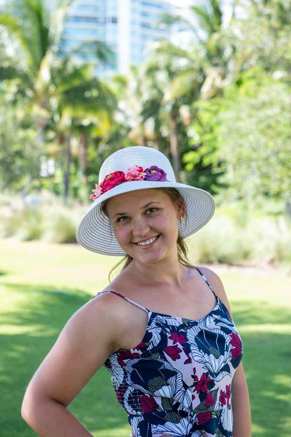 Mujer sonriente usando sombrero frente a las palmas foto de archivo