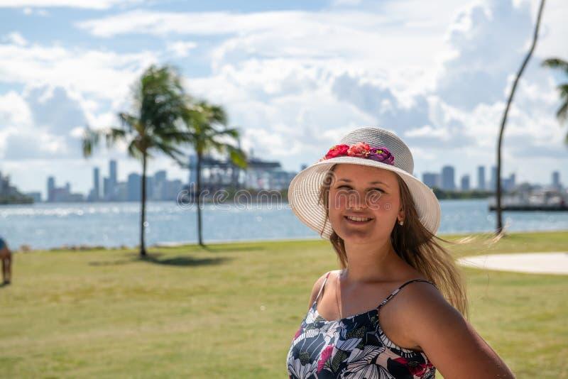 Mujer sonriente usando sombrero frente a Miami imagenes de archivo
