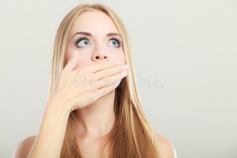 Mujer sorprendente que cubre su boca con la mano imagen de archivo
