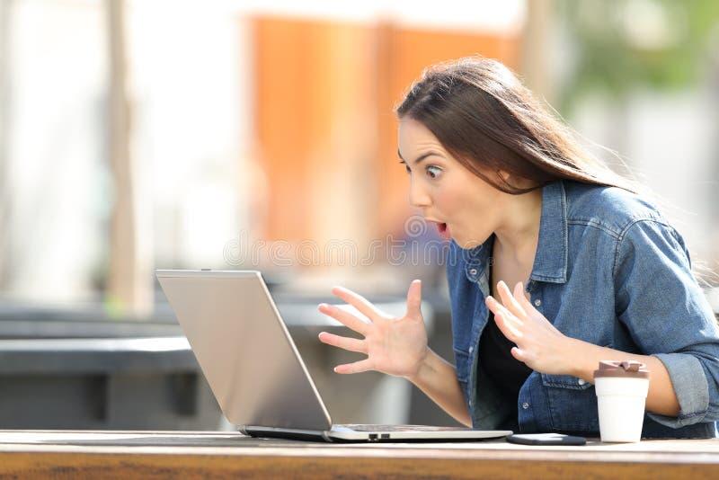Mujer sorprendente que encuentra el contenido en línea en el ordenador portátil en un parque imagen de archivo libre de regalías