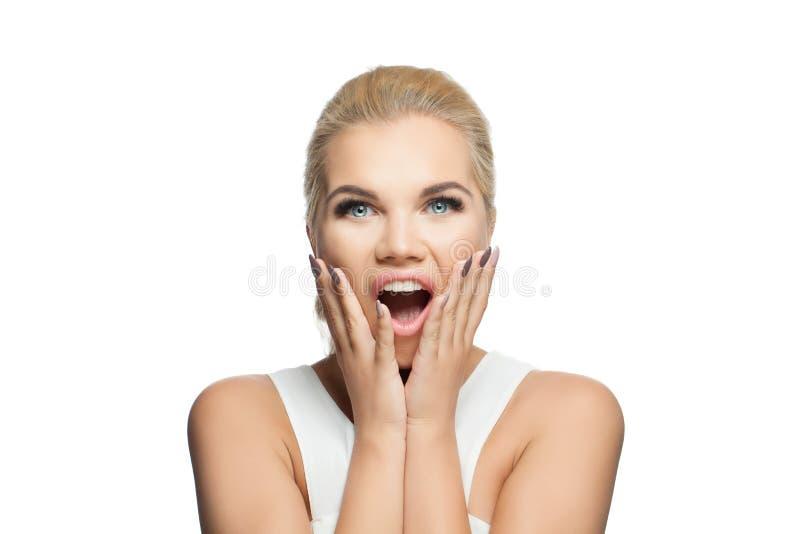 Mujer sorprendida aislada en el fondo blanco Muchacha de griterío chocada con la boca abierta imagenes de archivo