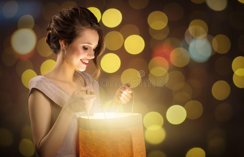 Mujer sorprendida atractiva que sostiene el bolso que hace compras m?gico foto de archivo