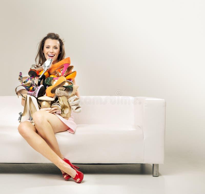 Mujer sorprendida con el montón de zapatos fotos de archivo