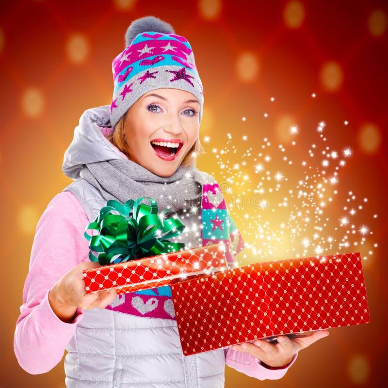 Mujer sorprendida con un regalo de la Navidad con el brillo mágico de b fotos de archivo libres de regalías