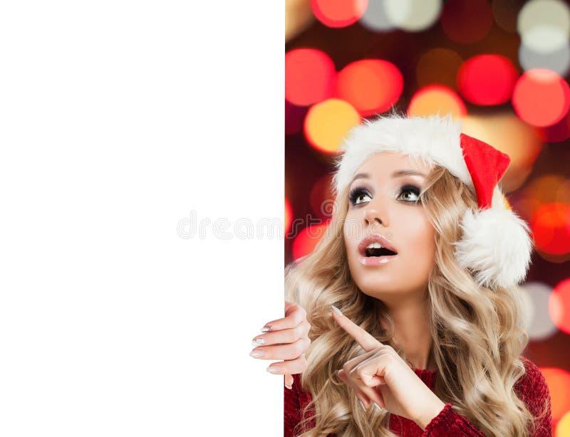Mujer sorprendida en el sombrero de Papá Noel que señala en bandera de papel vacía fotografía de archivo