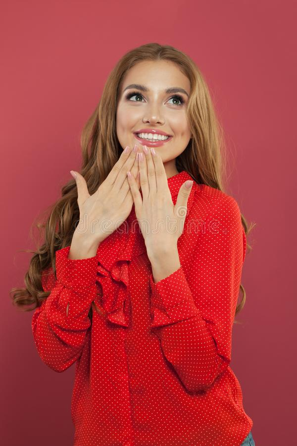Mujer sorprendida feliz con la sonrisa perfecta que mira para arriba Retrato bonito de la muchacha en fondo rosado colorido brill foto de archivo libre de regalías