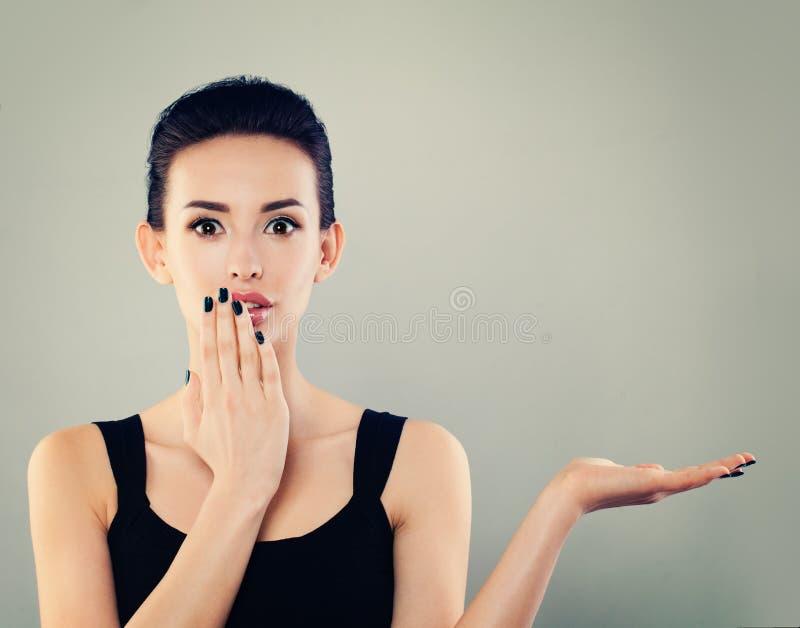 Mujer sorprendida feliz de la mujer que muestra la mano abierta vacía Modelo joven imagen de archivo libre de regalías