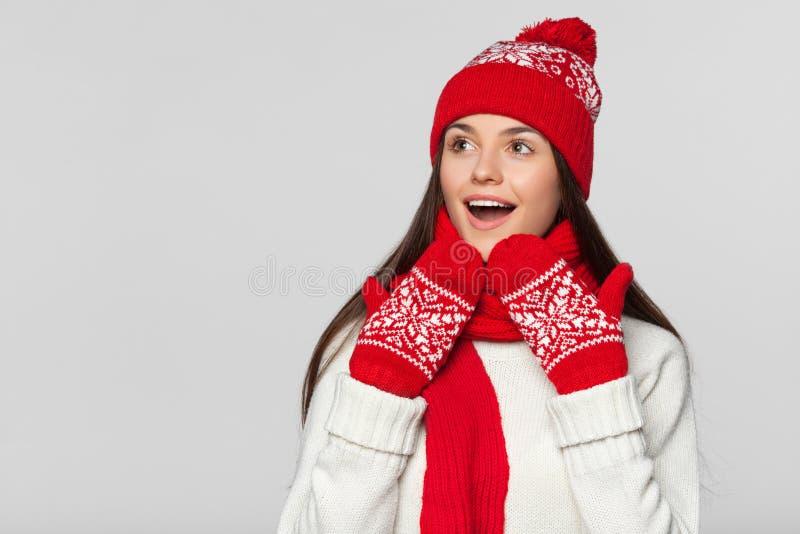 Mujer sorprendida feliz que mira de lado en el entusiasmo Muchacha emocionada de la Navidad que lleva el sombrero hecho punto y l imagen de archivo libre de regalías