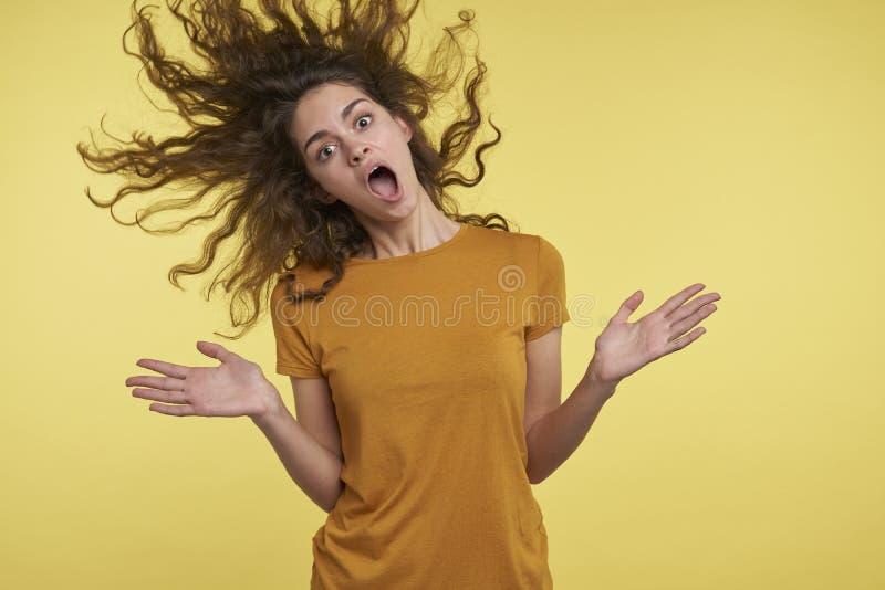 Mujer sorprendida joven bonita con el pelo que vuela rizado, ella feliz algo, bisela cree, aislado sobre amarillo fotografía de archivo libre de regalías