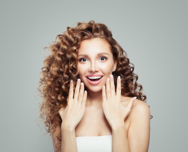 Mujer sorprendida Muchacha hermosa del estudiante con el pelo rizado largo Presentación de su producto Emoción positiva foto de archivo