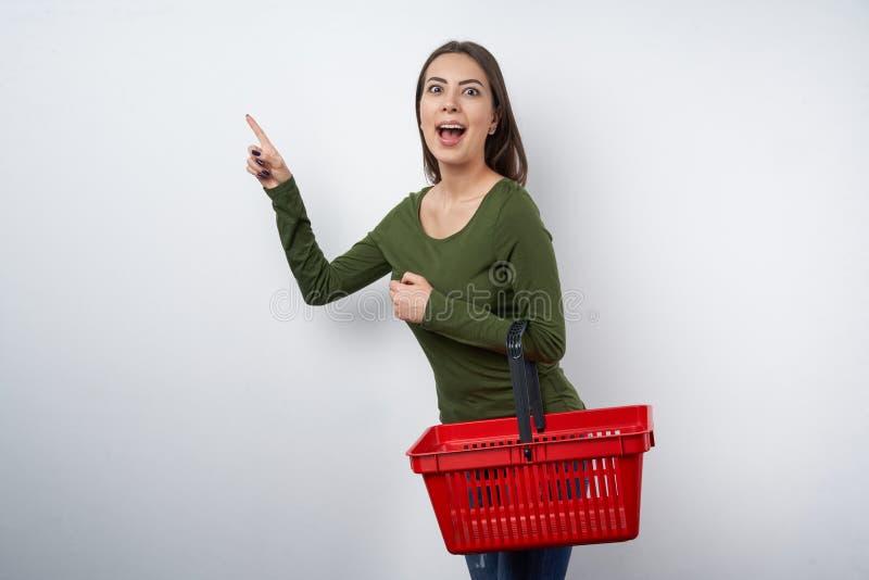 Mujer sorprendida que celebra señalar vacío de la cesta que hace compras fotos de archivo libres de regalías