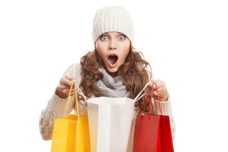 Mujer sorprendida que hace compras que sostiene bolsos Ventas del invierno fotos de archivo libres de regalías