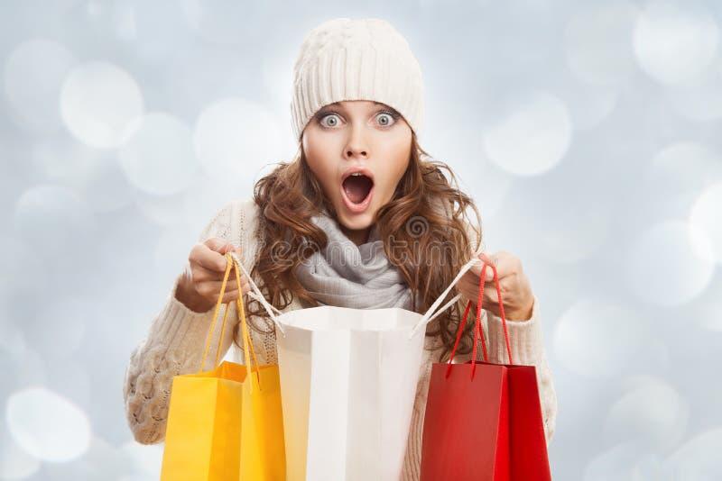 Mujer sorprendida que hace compras que sostiene bolsos Ventas del invierno fotografía de archivo