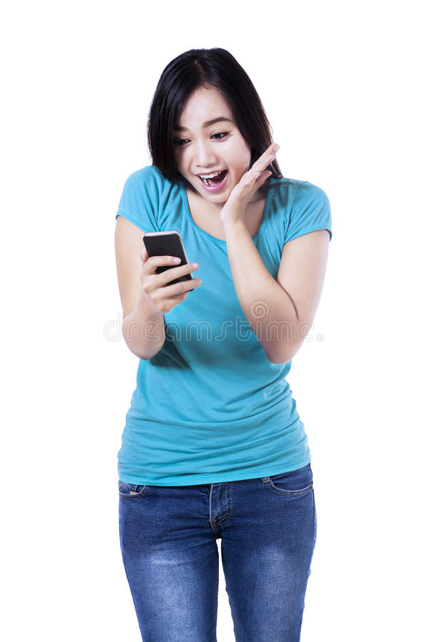 Mujer sorprendida que lee un mensaje de texto fotografía de archivo