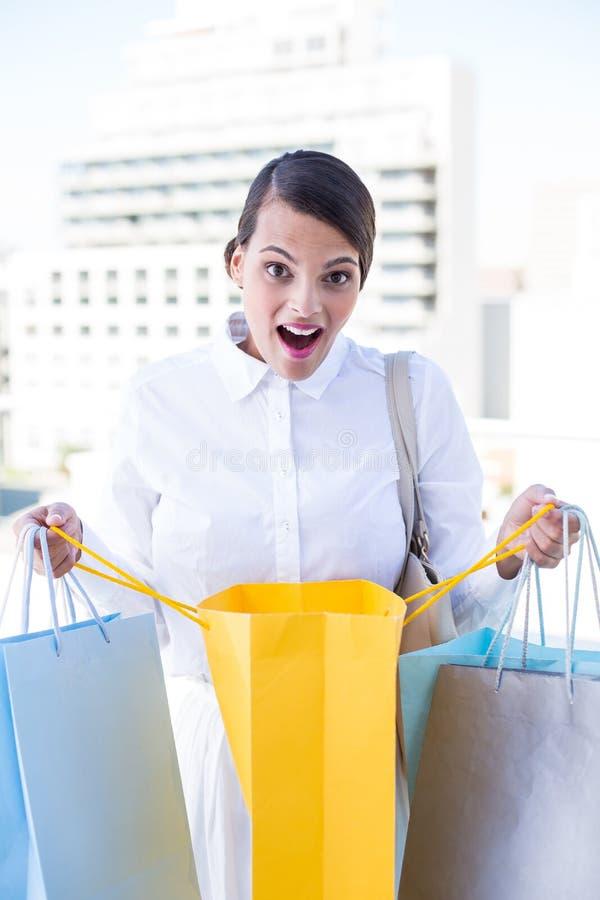 Mujer sorprendida que mira en bolso de compras imagen de archivo