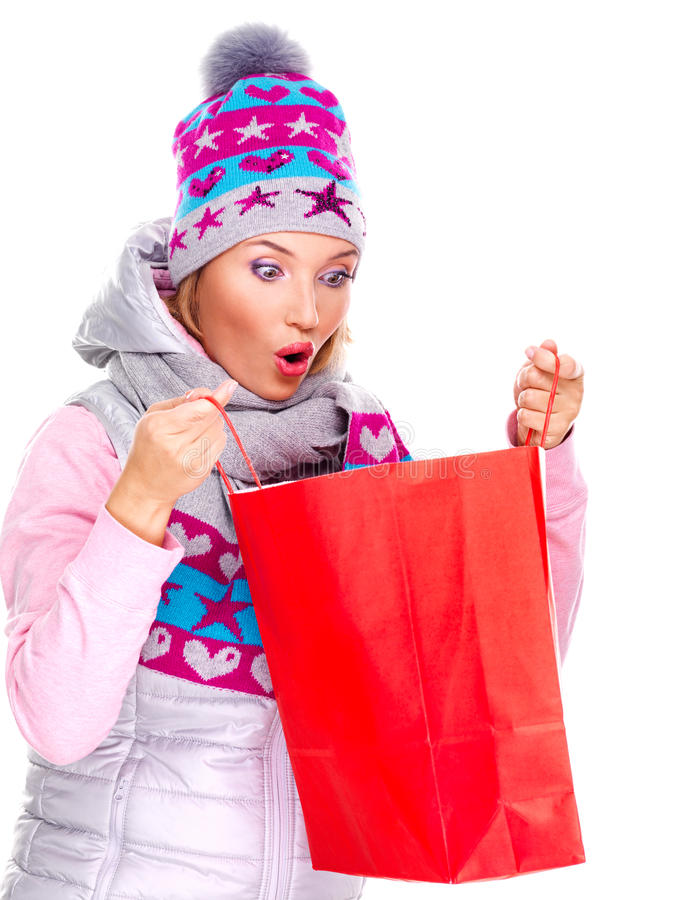 Mujer sorprendida que mira en los regalos en bolsos después de hacer compras foto de archivo
