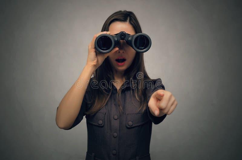 Mujer sorprendida que mira en prismáticos imagenes de archivo