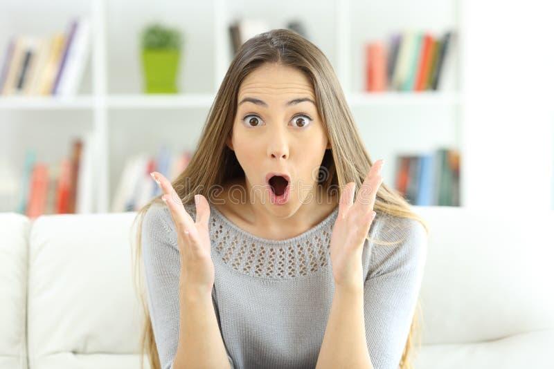 Mujer sorprendida que mira la cámara en casa fotos de archivo libres de regalías