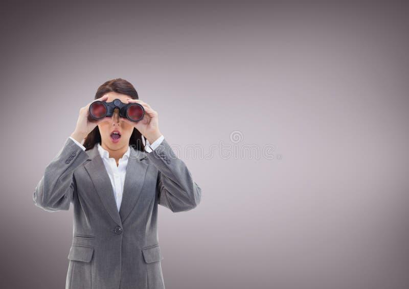 Mujer sorprendida que mira a través de los prismáticos contra fondo púrpura imagenes de archivo