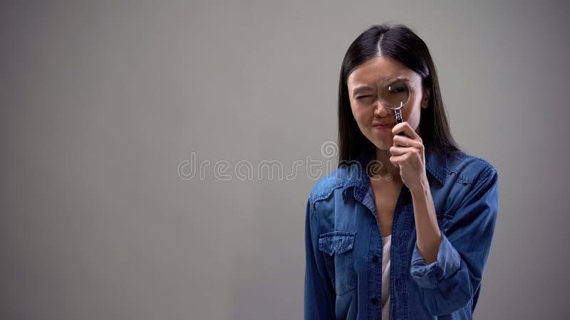 Mujer sospechosa que mira en la lupa, escudri?amiento detective privado fotos de archivo