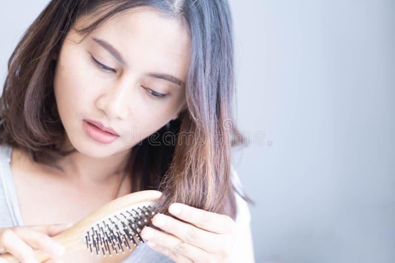 Mujer sosteniendo peine con serios problemas de pérdida de pelo para el cuidado de la salud champú y concepto de producto de bell foto de archivo