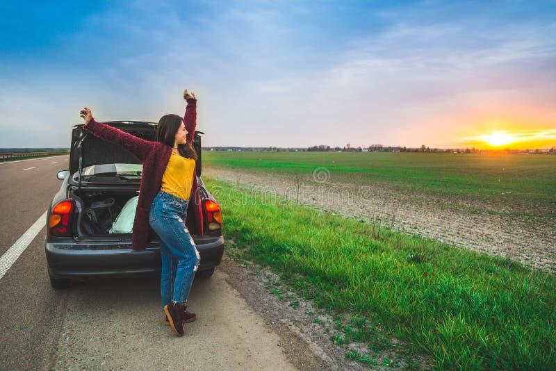Mujer stratching cerca de viaje largo del coche del coche fotografía de archivo