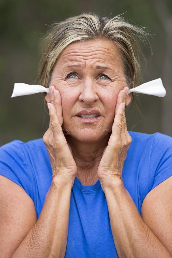 Mujer subrayada con la protección del ruido de los auriculares al aire libre fotos de archivo libres de regalías