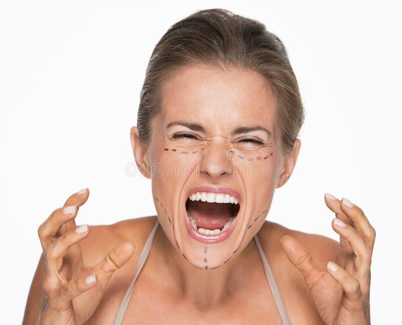 Mujer subrayada con las marcas de la cirugía plástica en cara imagenes de archivo