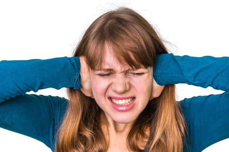 Mujer subrayada que cubre sus oídos para proteger contra fuerte ruido fotos de archivo