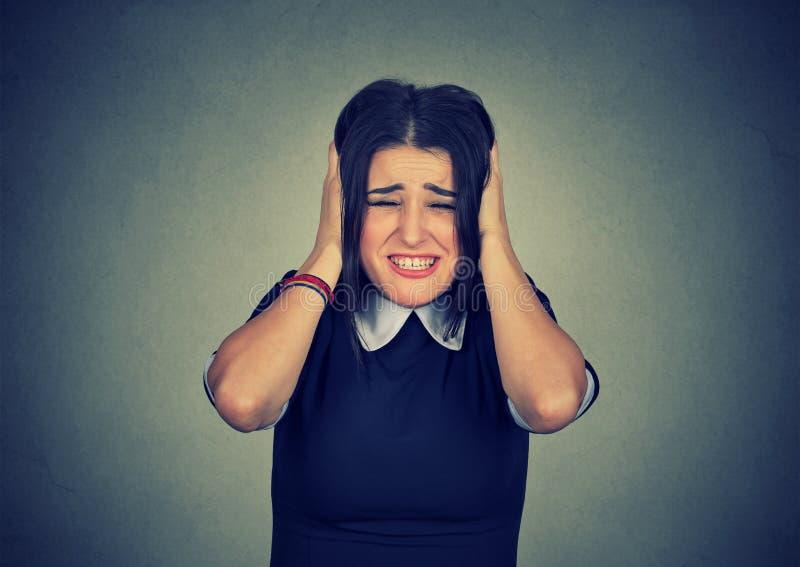 Mujer subrayada que exprime la cabeza con las manos foto de archivo