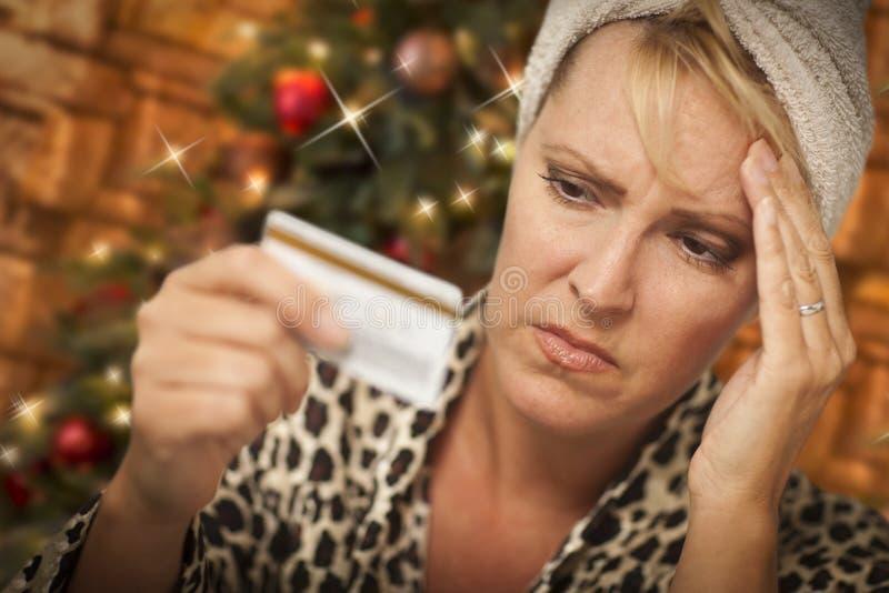 Mujer subrayada que sostiene la tarjeta de crédito delante del árbol de navidad imagen de archivo