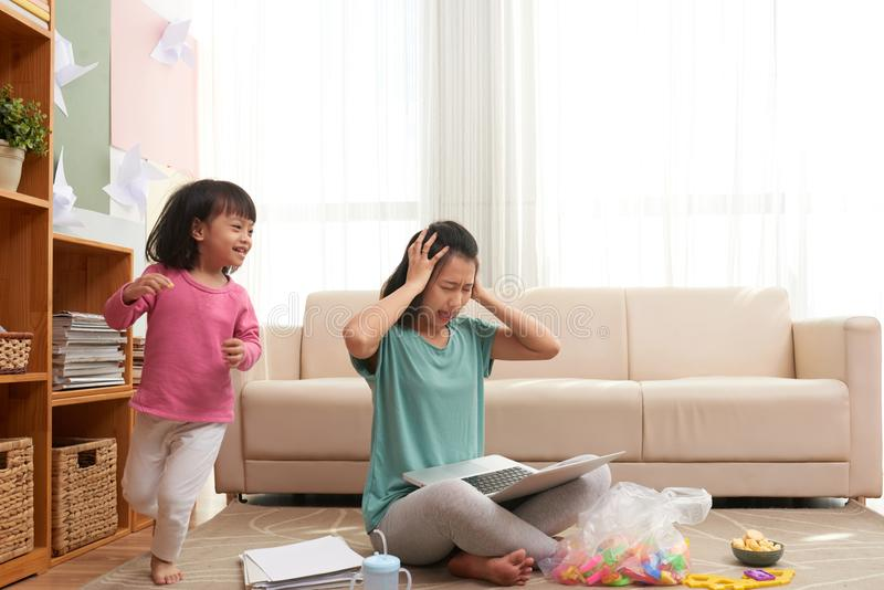 Mujer subrayada que trabaja en casa con el niño ruidoso fotos de archivo