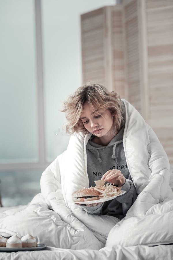 Mujer subrayada y sola que se sienta en cama y que come toda la mañana foto de archivo