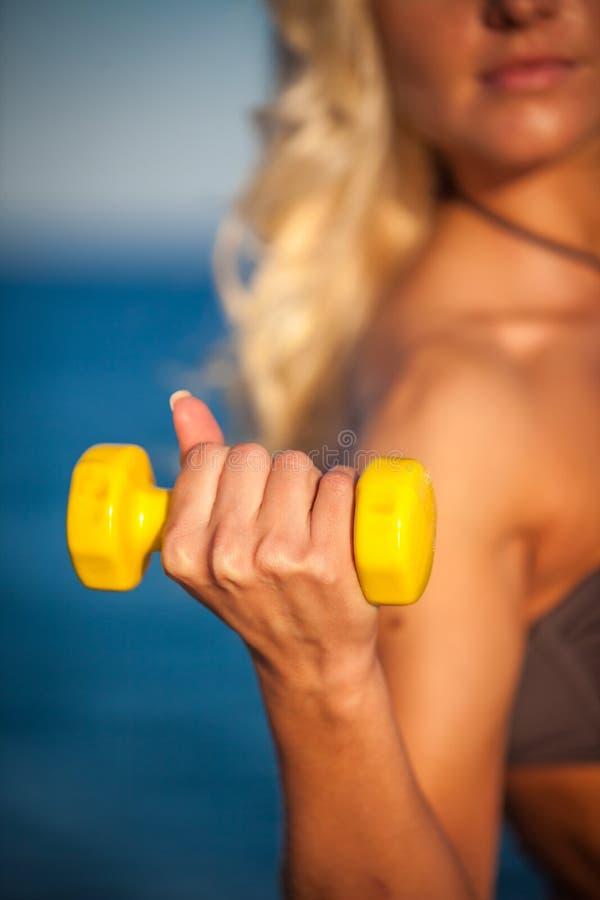 Mujer sudorosa de la aptitud que se resuelve con pesas de gimnasia fotos de archivo