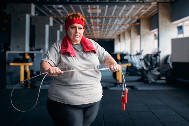 Mujer sudorosa gorda, ejercicio de la aptitud con la cuerda imagen de archivo libre de regalías