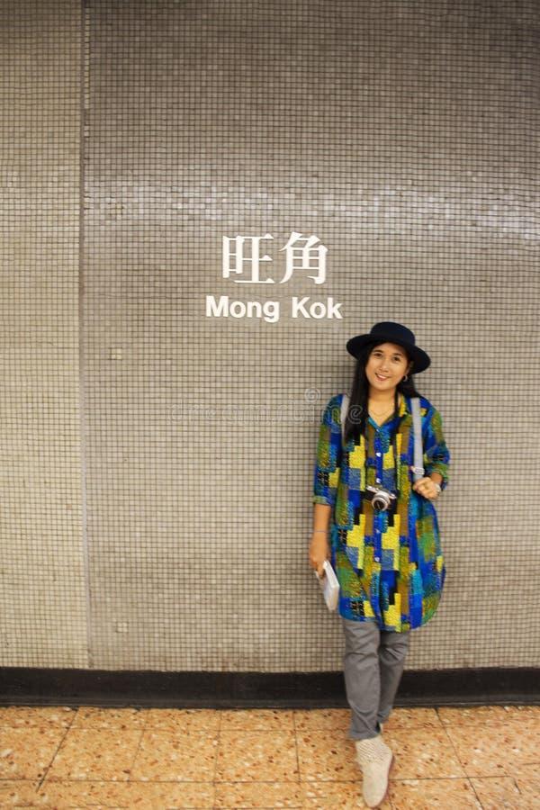 Mujer tailandesa de los viajeros que presenta para la foto de la toma en la pared en el ferrocarril de Mong Kok en Kowloon en Hon foto de archivo