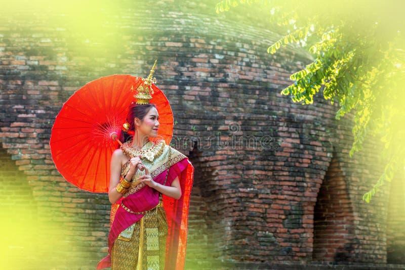 Mujer tailandesa en traje tradicional con el paraguas de Tailandia Traje tradicional femenino con el fondo tailandés del templo d imagenes de archivo