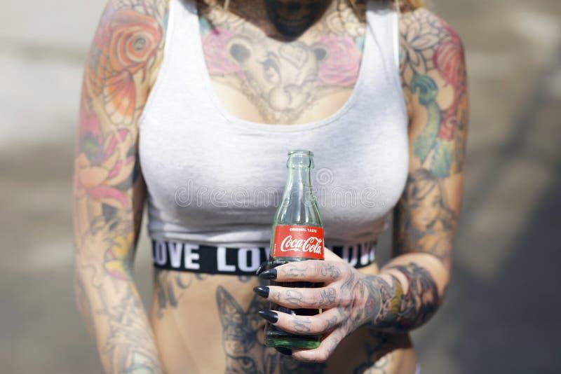 Mujer tatuada hermosa que sostiene una botella de original de Coca-Cola fotos de archivo