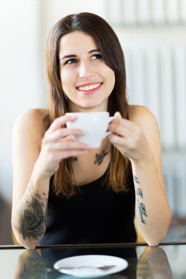 Mujer tatuada que goza de una taza de café imágenes de archivo libres de regalías