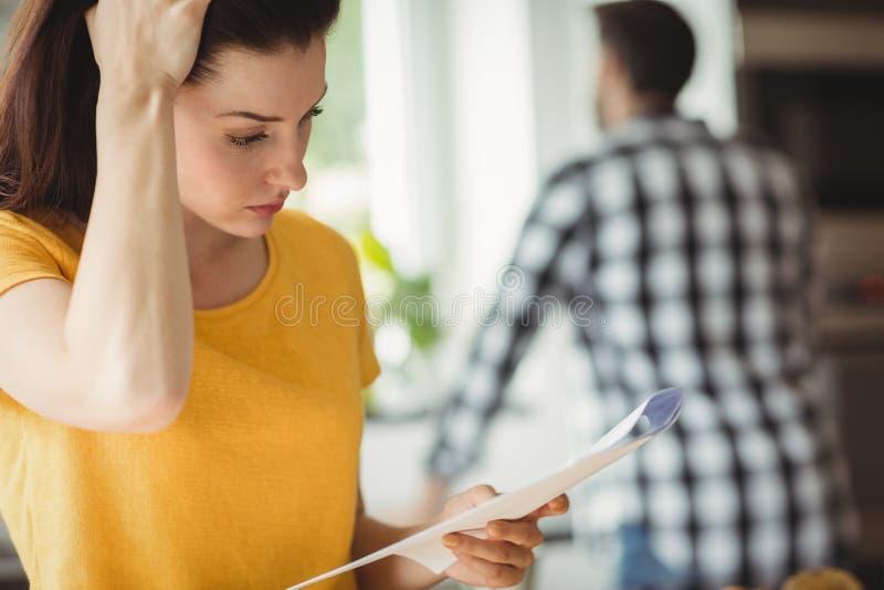 Mujer tensada que comprueba la cuenta en cocina imagen de archivo libre de regalías