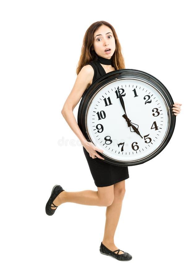 Mujer a toda prisa que corre con un reloj grande fotografía de archivo