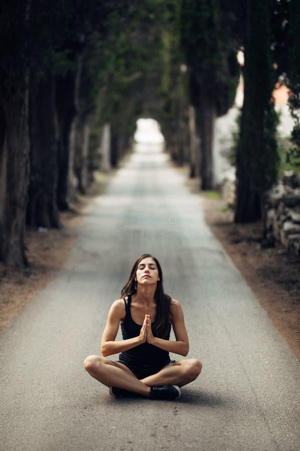 Mujer tranquila despreocupada que medita en naturaleza Encontrar paz interna Práctica de la yoga Forma de vida curativa espiritua foto de archivo