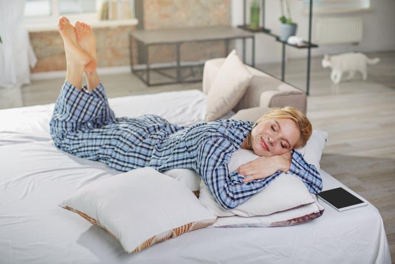 Mujer tranquila que duerme en la almohada en casa imagenes de archivo