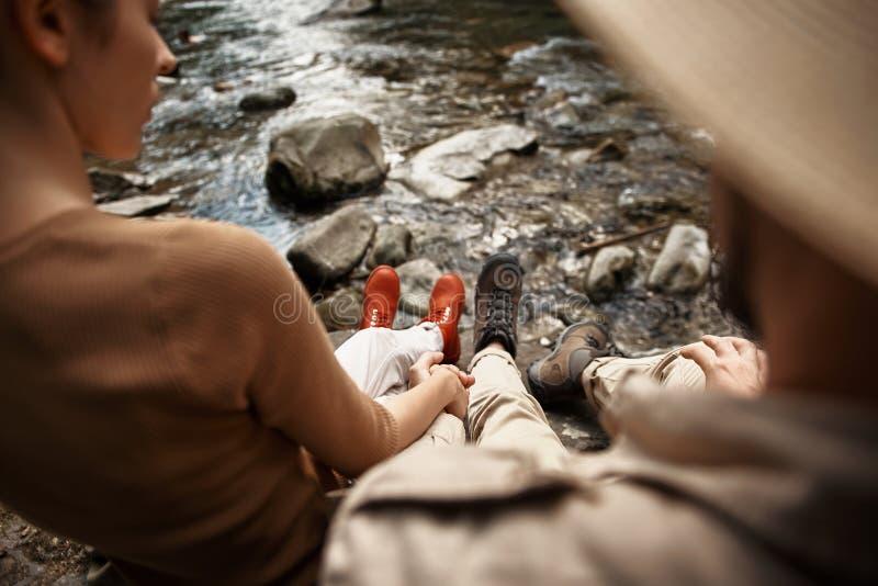 Mujer tranquila que lleva a cabo la mano de su novio mientras que se sienta cerca del río fotos de archivo
